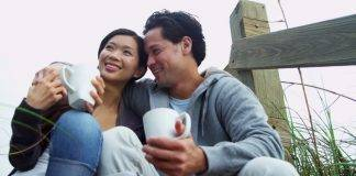 Asian Chinese couple sipping coffee on the beach