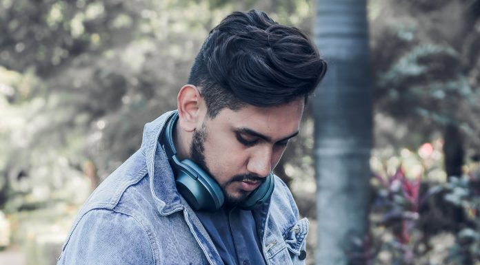 Man with dark hair and earphones looking down