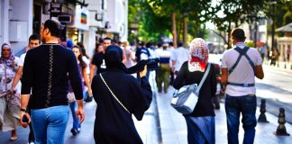 Women wearing burqa walking down the street in a crowd of people