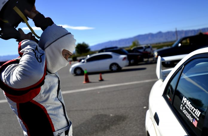 Man with helmet and white mask approaching a race car