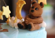 Small brown bear sitting by a baby's table