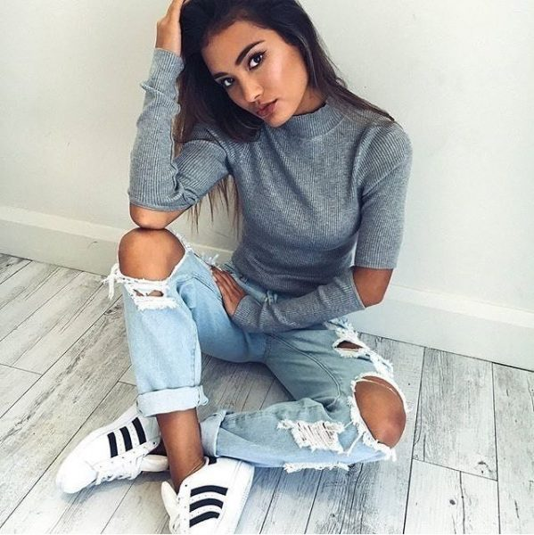 Gorgeous girl sitting on floor with a pair of ripped boyfriend jeans and white tennis shoes