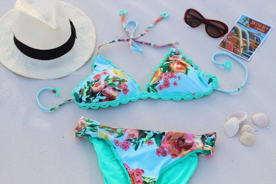 Swimsuit two piece with hat and glasses on white sand
