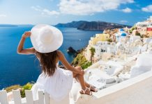 Lady in all white overlooking the blue waters of Greece