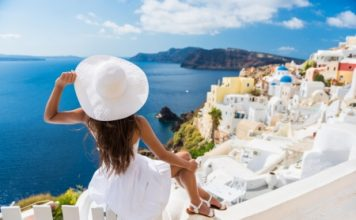 Travel Tips for Single Women Lady in all white overlooking the blue waters of Greece