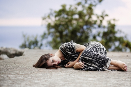 Woman laying down in the middle of the road