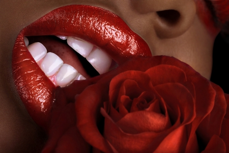 Woman of color with full lips, white teeth and a rose
