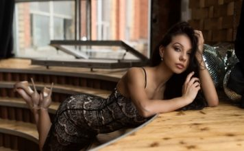 Fake dating profiles Beautiful woman dressed in black kneeling on a table