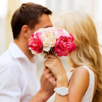 why is kissing so important to relationships? man and woman hiding a kiss with a handful of flowers