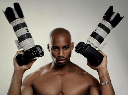 shirtless man holding cameras in each hand