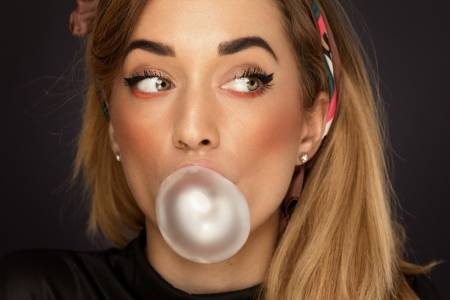 Is Bad Breath in Your Way of Dating? See the woman blowing gum bubbles with blonde hair and brown eyes