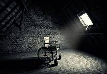 Dating someone with spinal cord injury - picture of an empty wheelchair in a loft with brick walls and a sky light