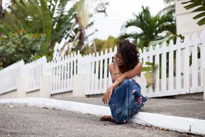 jamaican woman sitting laughing on sidewalk by white picket fence