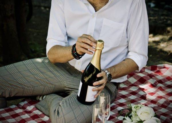 date ideas at home man opening bottle of wine on picnic photo Jelleke Vanooteghem