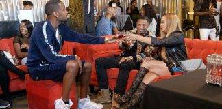 Stevie J and Faith Evans sitting down with friends over drinks