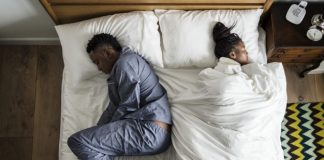 African American couple sleeping back to back