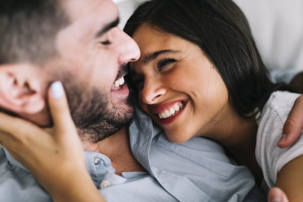 young woman smiling at man cuddling  600x400 - The Most Sensitive Parts of a Man to Get Him in the Mood