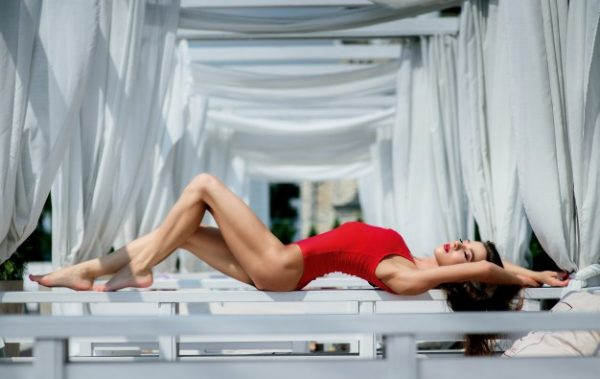 11 Signs She's Thinking of Cheating On You pretty woman in red swimsuit lies on white sofa outside 1304 5486 600x379 - 11 Signs She's Thinking of Cheating On You