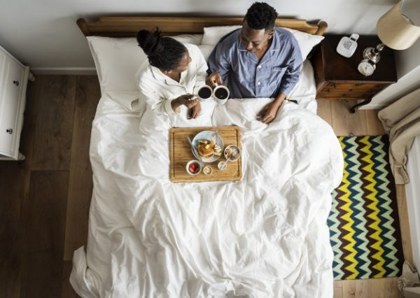 Find Out Which Zodiac Sign Will Make the Best Husband African American couple in bed having a breakfast in bed
