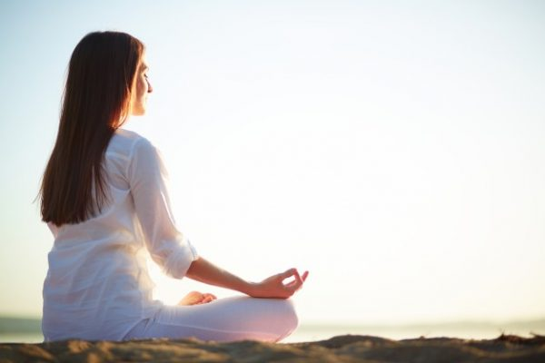 self care woman sitting in yoga pose on the beach 1098 1454 600x400 - Top 11 Basic Self-Care Tips to Reduce Stress