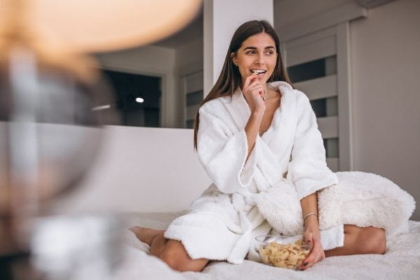 Why Some People Naturally Attract Long-Term Relationships pretty woman sitting on bed, snacking in white bathrobe