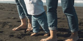 postpartum exercise feet baby parents walking sandy coastline 23 2148134549